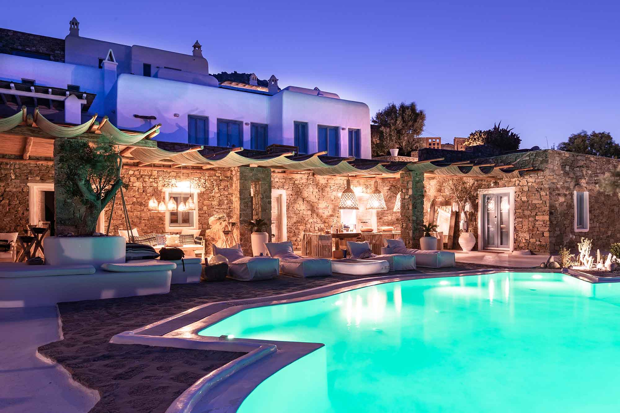 RENT A LUXURIOUS VILLA BY THE SEA IN MYKONOS - VILLA KARKOS - blue swimming pool at night